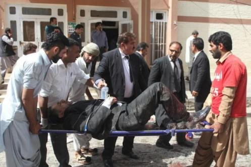 First responders and volunteers transport an injured man away from the scene of a bomb blast outside a hospital in Quetta